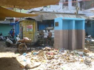 Een man wast zich in de stad. Rechts de wc.